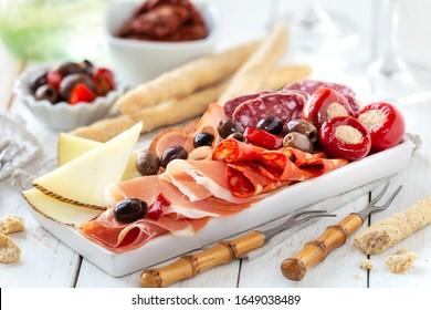 Köstliche Fleischplatte mit Käse, würzigen Oliven und gefülltem Kirschpaprika als Aperitif mit Brotstöcken. Traditionelle spanische Tapas mit Schinken, Choriso, Lomo iberico, Fuchs- und Ziegenkäse