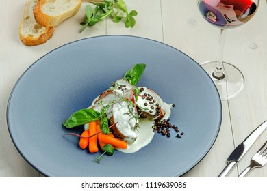 Delicious meat steak medallions with cream sauce on a luxurious plate served with bread and red wine. Healthy food made of meat and fresh salad.