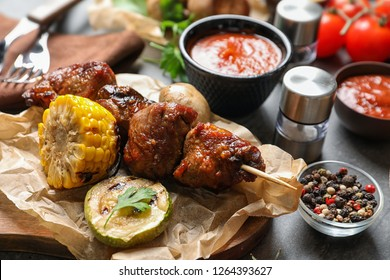 Delicious meat and vegetables served for barbecue party on gray table