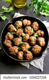 Delicious meatballs in frying pan on black stone background. Top view