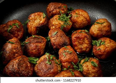delicious meatballs with parsley in a pan on a black old wooden table
