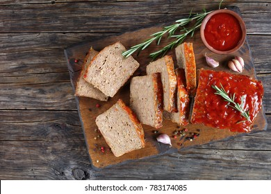 delicious meatloaf cut in slices with garlic, rosemary, and tomato sauce on cutting board on dark wooden table, view from above