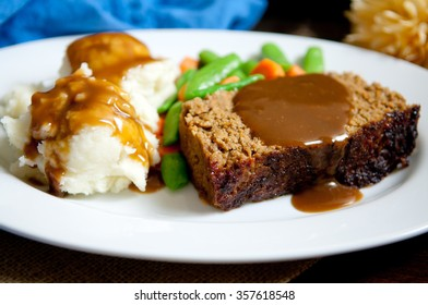 delicious meatloaf with mashed potatoes, gravy and fresh vegetables