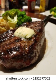 Delicious medium baked grilled New York Steak. Presentation with potato roots and broccoli.