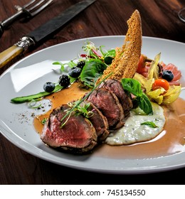 Delicious medium rare meat steak with sauce and salad on a plate. Healthy food made of meat fillet and fresh herbs on a wooden table.