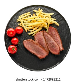 Delicious medium rare steak with French fries and fresh cherry tomatoes on a black plate. Classic meat meal isolated on white background. Top view, directly above shot.