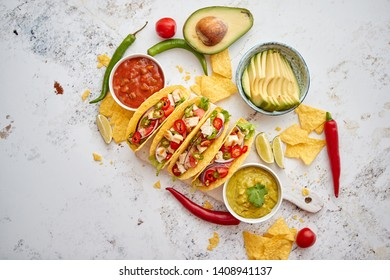 Delicious Mexican fresh crispy tacos are served on wooden board. Stuffed with grilled chicken, spicy pepper, onion, tomato and more. With salsas on side.