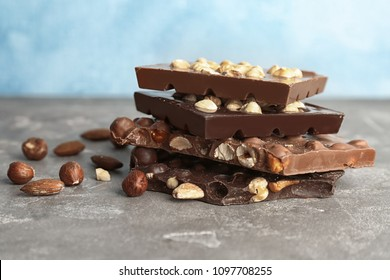 Delicious milk and dark chocolate bars with nuts on table