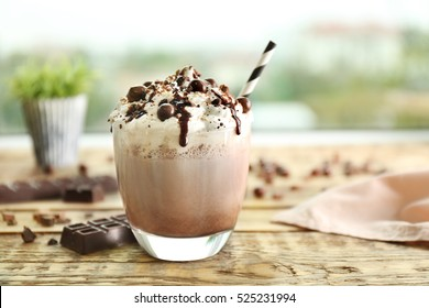 Delicious milk dessert with chocolate on wooden table and blurred background