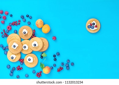 Delicious mini smile pancakes with berries on blue surface, top view. Flat lay, top view sweet food background.