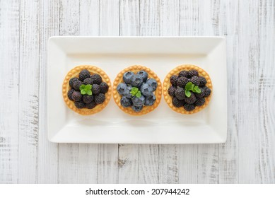 Delicious mini tart with fresh blackberries and blueberries on wooden background