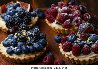 Delicious mini tarts with fresh berries and custard on wooden background