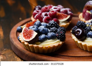 Delicious mini tarts with fresh berries and custard on wooden cutting board
