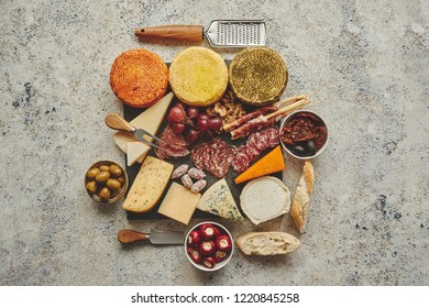 Delicious mix of different snacks and appetizers. Spanish tapas or italian antipasti on a black stone plate. View from above. Placed on stone table.