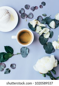 Delicious morning cup of coffee with white peony flower, some petals and eucalyptus leaves, white marshmallow in a saucer on the blue background, top view, flat lay