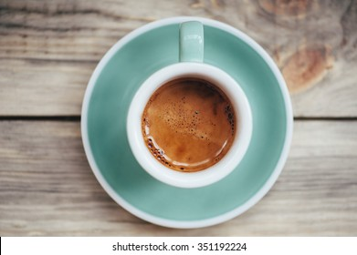 Delicious morning cup of espresso coffee with beautiful tiger crema on the wooden table rustic background