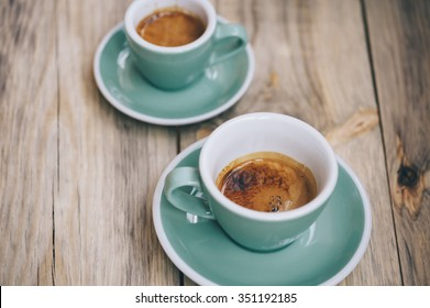 Delicious morning two cups of espresso coffee with beautiful tiger crema on the wooden table rustic background