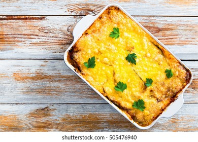 delicious moussaka  in gratin dish,  authentic recipe -  layers of eggplant, minced meat, tomato, bechamel sauce and cheese baked in oven decorated with parsley, on old wooden planks, view from above
