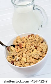 Delicious muesli in white bowl and milk on wooden table