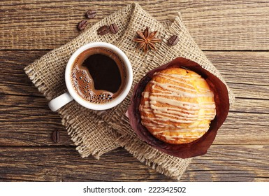 Delicious muffin and cup of hot coffee on vintage wooden table. Top view