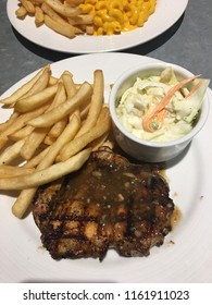Delicious mushroom grilled chicken with side dishes of French fries and coleslaw. Typical western dish for a fine dinner.