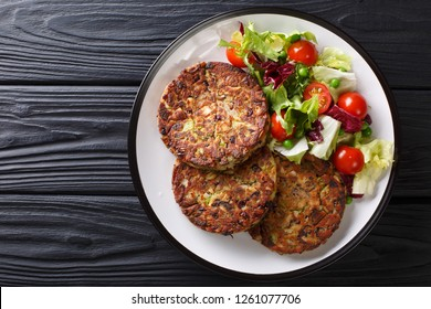 Delicious mushroom vegetable patties served with fresh salad on a plate close-up on the table. horizontal top view from above