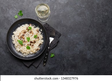 Delicious mushrooms risotto dressed with parmesan cheese and parsley. With white wine glass. Top view with copy space