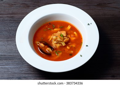 Delicious mussel soup in white plate on black background