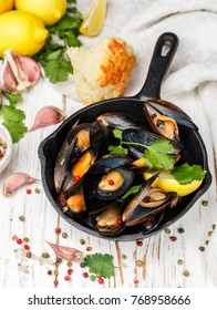 Delicious mussels in white wine with lemon, garlic, herbs and spices in a cast iron skillet . Baguette, Cilantro and pepper. Seafood. Clams in the shells. Snack for gourmets. Selective focus