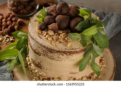 Delicious naked coffee and hazelnuts cake on table rustic wood kitchen countertop.
