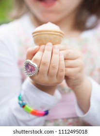 delicious natural red ice cream in hand palm, child. plastic ring differs heart.