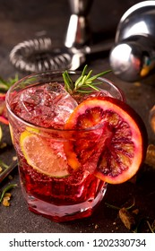Delicious negroni cocktails with campari, gin, vermouth, and a citrus orange twist. Refreshing summer drink on stone or concrete background. Holiday aperitif for Christmas party.