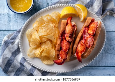 Delicious New England style lobster rolls with potato chips and melted butter on a wood table top,