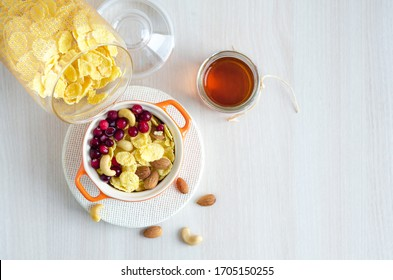 delicious and nutritious breakfast. healthy lifestyle. corn flakes topped with berries, nuts, honey. top view, copy space.
