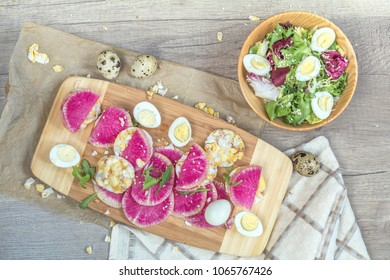 Delicious nutritious cereal breads with cream cheese and red radishes, fresh salad with lettuce and quail eggs on wooden board. Healthy eating concept.