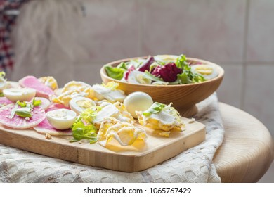 Delicious nutritious cereal breads with cream cheese and red radishes, fresh salad with lettuce and quail eggs on wooden surface. Healthy eating concept.