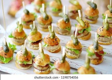 Delicious one bite mini burgers served on a party or wedding reception. Plates with assorted fancy finger food snacks on an event party or dinner.