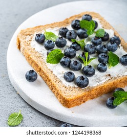 Delicious open sandwich with goat cheese and blueberries for breakfast or lunch on marble board. Food background.