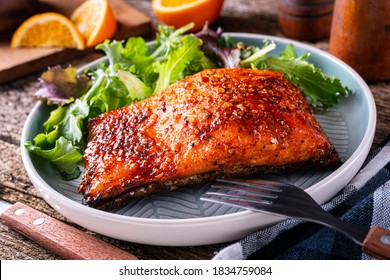 Delicious orange and ginger glazed planked salmon with side greens.