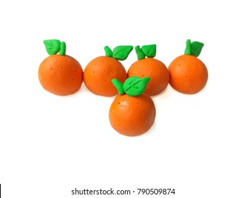 Delicious oranges made from plasticine clay arranged are beautiful on white background,   leader placed in front of other pieces dough fruits