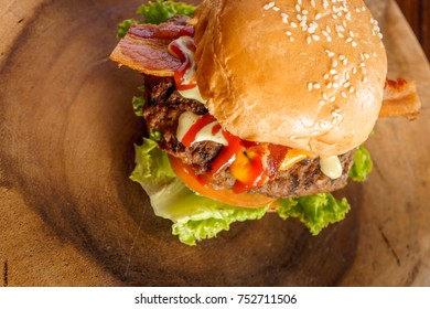 delicious organic burger with purple onion, lettuce, bacon, and garlic sauce with spices, on a colorful background on a wooden table.