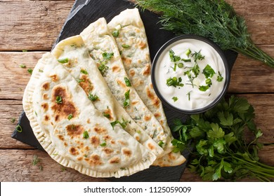 Delicious organic flat bread qutab stuffed with herbs served with yogurt close-up on the table. Azerbaijani cuisine. horizontal top view from above