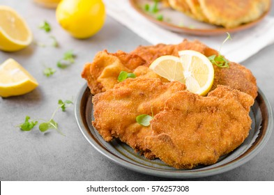 Delicious original schnitzel with potato pancakes, fresh juice, pancakes with garlic and herbs