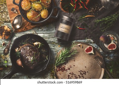 Delicious outdoor table with steak, baked potatoes on dark background, top view. Rustic food cooking.