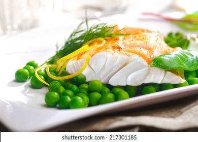 Delicious oven baked fish or grilled fillet or steak with peas, a mangetout pod, lemon zest and fresh dill for a nutritious seafood dinner