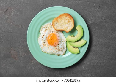 Delicious over easy egg with toast and avocado slices on kitchen table