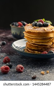 Delicious pancake with blueberries, raspberries and icing sugar in blue dish on rust table.