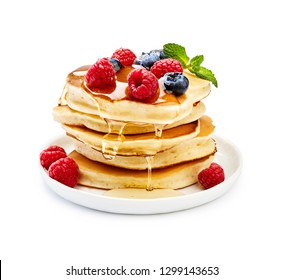 Delicious pancakes with berries, honey or maple syrup. Homemade pancakes and sweet syrup on white plate isolated.