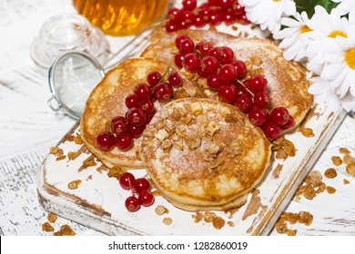 delicious pancakes with berries and honey on a white wooden board, top view horizontal