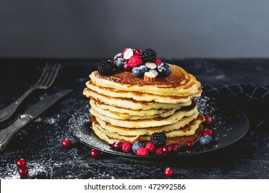 Delicious pancakes with berries on dark slate background